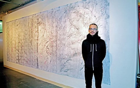 Oyama Enrico Isamu Letter, the artist, with one of his murals. Photo by Dakota Santiago
